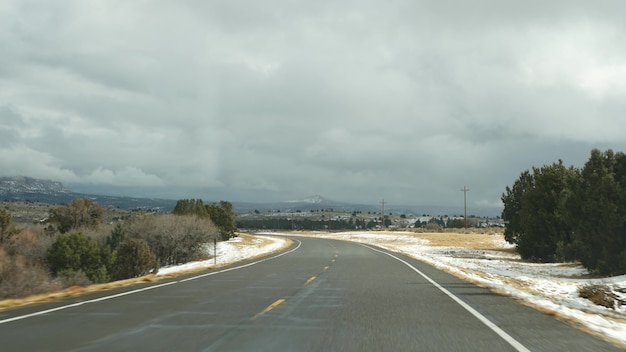 Wycieczka samochodowa w usa z syjonu do bryce canyon, jazda samochodem w stanie utah. autostop podróżujący po ameryce, route 89 do dixie forest. zimowa podróż lokalna, spokojna atmosfera i śnieżne góry. widok z samochodu.