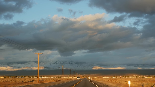 Wycieczka samochodowa z doliny śmierci do las vegas w stanie nevada usa. autostop podróżowanie po ameryce. podróż autostradą, dramatyczna atmosfera, góra o zachodzie słońca i pustynia mojave. widok z samochodu.
