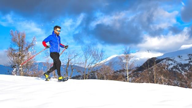 Wycieczka w rakietach śnieżnych samotnego młodego sportowca