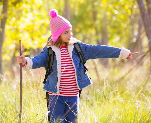 Wycieczkować dzieciak dziewczyny wskazuje palec w autum lesie z plecakiem