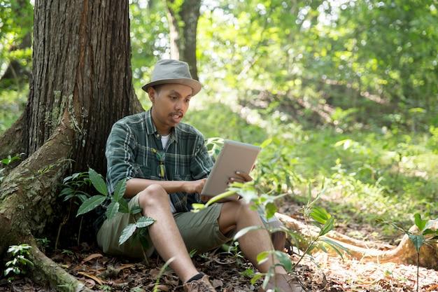 Wycieczkowicz człowiek zrobić sobie przerwę i przy użyciu komputera typu tablet