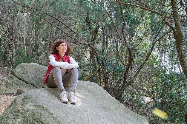 Wycieczkowicz kobieta siedzi na kamieniu w górach
