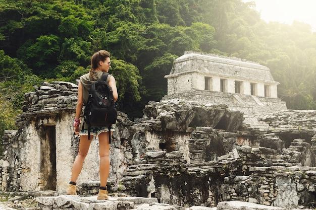 Wycieczkowicz kobieta z plecakiem patrząc na starożytne ruiny majów