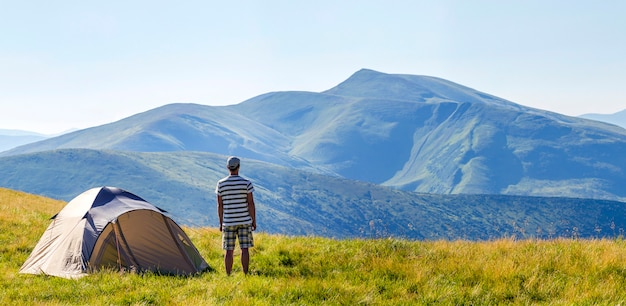 Wycieczkowicz mężczyzna stoi blisko campingowego namiotu w karpackich górach. turysta podziwiać widok na góry. koncepcja podróży.