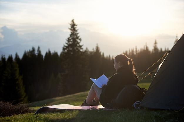 Wycieczkowicz młoda kobieta czyta książkę w pobliżu namiotu wieczorem o zachodzie słońca