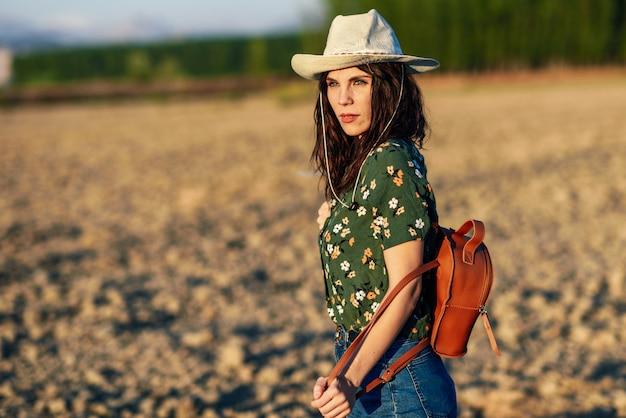 Wycieczkowicz młoda kobieta wycieczkuje w wsi przy zmierzchem