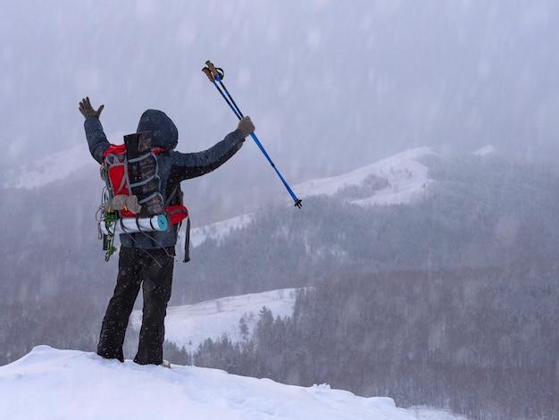 Wycieczkowicz na szczycie góry z podniesionymi rękami. zwycięstwo. koncepcja turystyki.