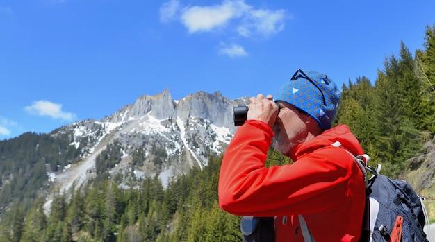 Wycieczkowicz patrzeje lornetki w góra krajobrazie