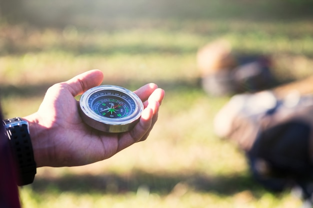 Wycieczkowicz szuka kierunku z kompasem w lesie.
