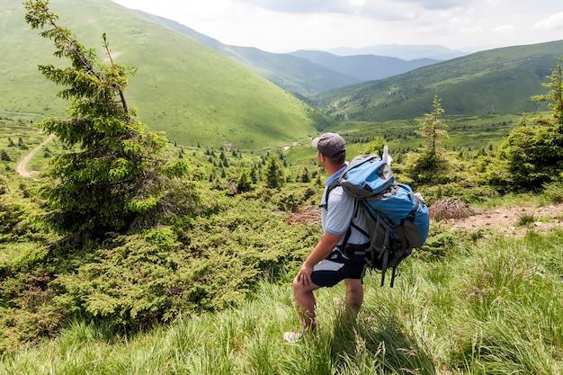 Wycieczkowicz z plecakiem cieszy się wschód słońca od wierzchołka góry