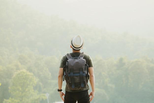 Wycieczkowicz z plecakiem stoi na ulicie i cieszy się górę pojęcie sukcesu