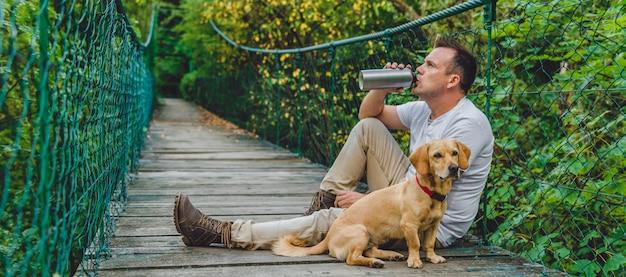 Wycieczkowicz z psem odpoczywa na drewnianym zawieszenie moscie