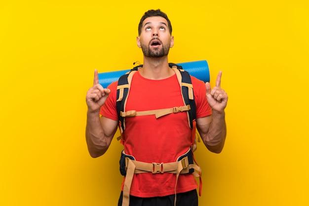 Wycieczkowicza mężczyzna wskazuje up nad żółtym tłem