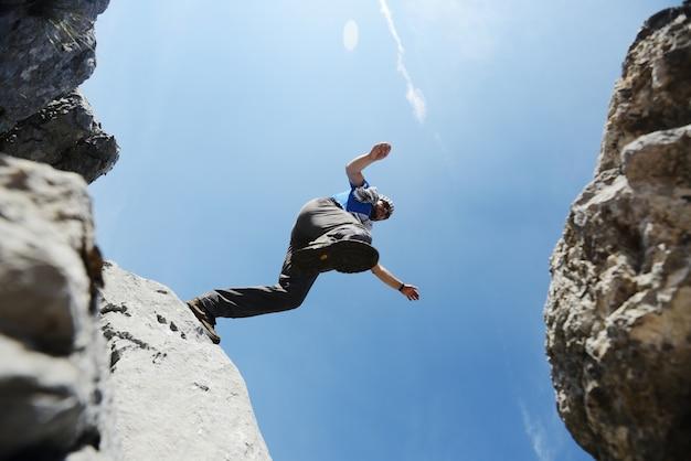 Wycieczkujący mężczyzna skacze nad górami sukces