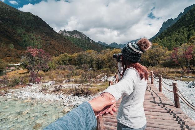 Wycieczkujący potomstwa dobiera się podróżnika patrzeje pięknego krajobraz przy yading rezerwatem przyrody, podróż stylu życia pojęcie