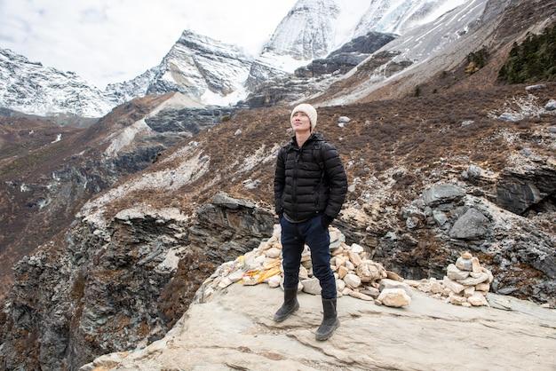 Wycieczkuje mężczyzna cieszy się w śnieg szczytu górze przy jesienią, ludzie podróżuje pojęcie