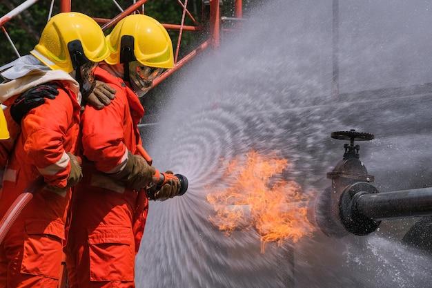 Wyciek gazu z rury i zaworu. płomień z wycieku gazu. gaszenie pożarów przy pomocy gaśnic i węża gaśniczego.
