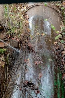 Wyciek wody z uszkodzonych punktów spawania w rurze małej elektrowni wodnej