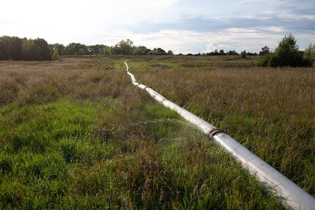 Wyciekająca rura wodna z strumieniem z otworu w polu na świeżym powietrzu.