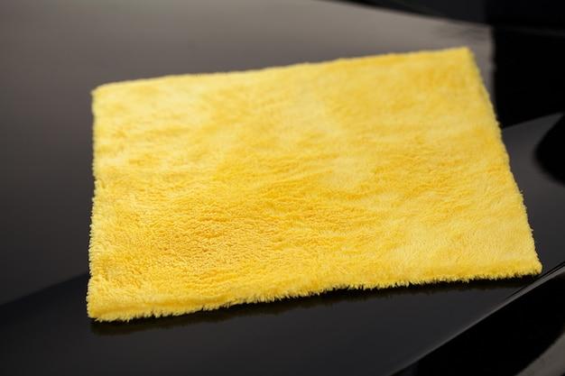 Wycieranie panelu luksusowego samochodu z żółtą mikrofibrą
