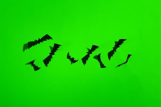 Wycinane z papieru nietoperze w zielonym neonowym świetle. motyw halloween