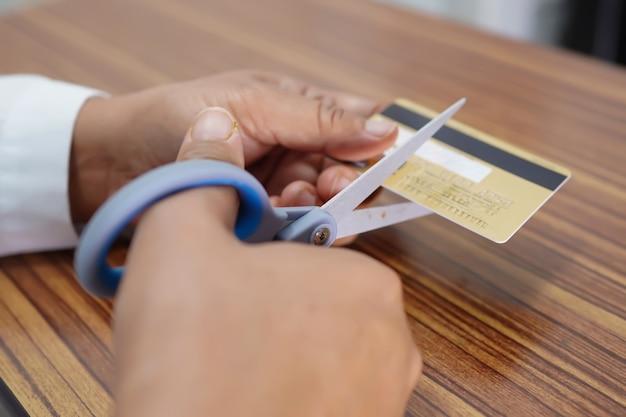 Wycinanie karty kredytowej lub debetowej nożyczkami po anulowaniu do użycia.