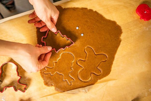 Wycinanie kształtów piernikowych. młoda kobieta wycina pierniki na papierze do pieczenia bruna. czerwone pierniki.