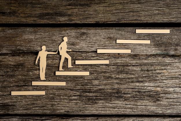 Wycinanki z papierowych mężczyzn, z których jeden pomaga popchnąć od tyłu, a drugi wspina się po schodach po rustykalnym drewnie. koncepcja partnerstwa.