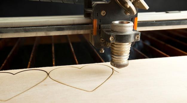 Wycinarka laserowa tnie drewnianą deskę