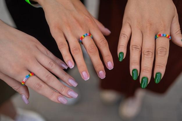 Wycinek trzech dziewczyn pokazujących stylowy manicure trzymający palce na czarnej skórzanej torebce diff...