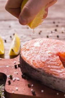 Wyciskanie świeżego soku z cytryny na filety rybne. gotowanie stek z łososia.
