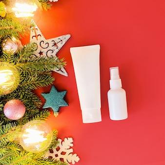 Wycisnąć plastikową rurkę, butelkę z rozpylaczem i świąteczny wystrój na czerwonym stole. .