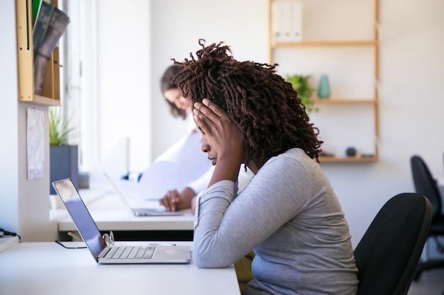 Wyczerpana amerykanin afrykańskiego pochodzenia kobieta patrzeje laptop
