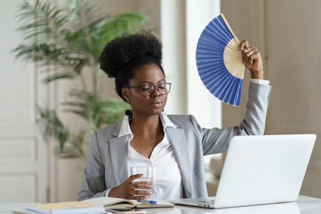 Wyczerpana bizneswoman zmęczona gorącym falującym papierowym wentylatorem na świeże powietrze w miejscu pracy pracuje na laptopie