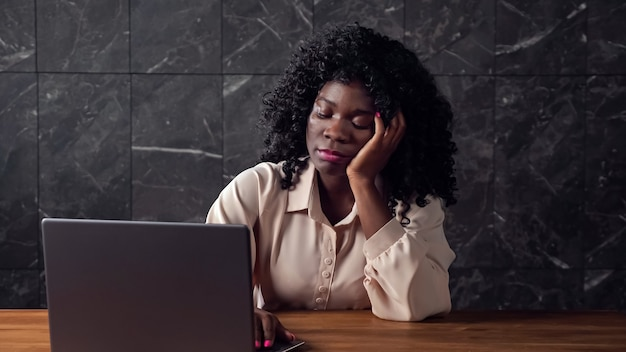 Wyczerpana czarna kobieta z typami kręconych włosów na szarym laptopie leniwie i ziewa siedząca przy brązowym drewnianym stole w biurze późnym wieczorem