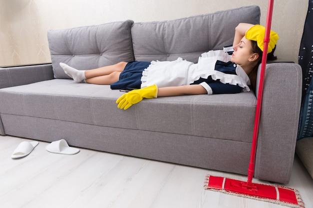 Wyczerpana gospodyni relaksująca się w pracy, leżąca na kanapie w mundurze, ucinająca sobie drzemkę z mopem obok