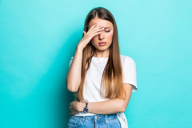 Wyczerpana kobieta dotyka głowy stojąc z zamkniętymi oczami
