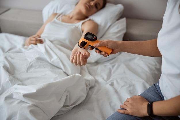 Wyczerpana kobieta leżąca w łóżku i wyciągająca rękę patrząc na termometr