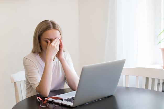 Wyczerpana kobieta ma ból głowy po pracy na laptopie