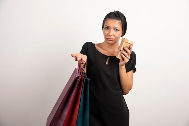 Wyczerpana kobieta niosąca kolorowe torby na zakupy i filiżankę kawy.