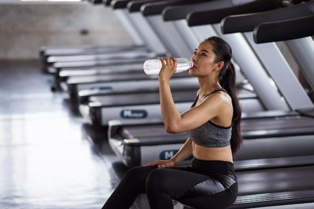 Wyczerpana kobieta pije wodę po uruchomieniu w siłowni