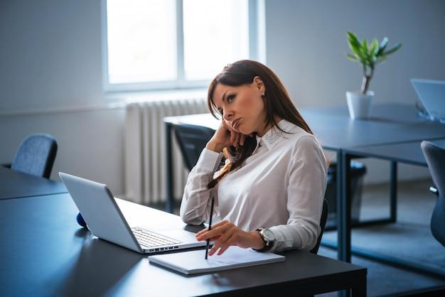 Wyczerpana kobieta siedzi przed komputerem