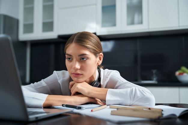 Wyczerpana kobieta siedzi przy stole i pracuje na laptopie