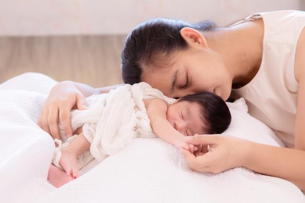 Wyczerpana mama śpi z córeczką i trzyma się za ręce