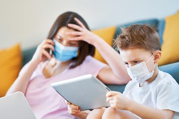 Wyczerpana matka próbująca pracować w domu i opiekująca się synem podczas pandemii koronawirusa