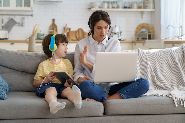 Wyczerpana matka siedzi na kanapie w domu podczas blokady, praca na laptopie, dziecko odwraca uwagę od pracy
