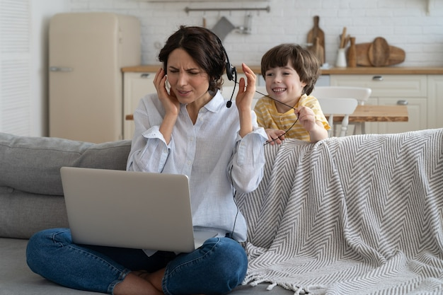 Wyczerpana matka siedzi na kanapie w domu, pracuje na laptopie, dziecko jest rozproszone i zwraca się o uwagę