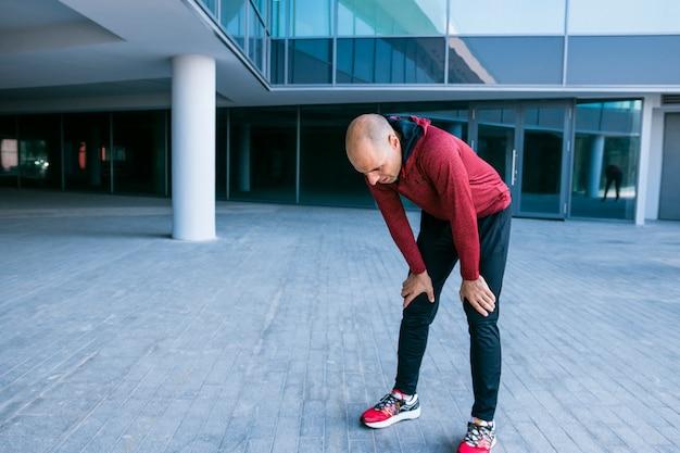 Wyczerpana męska atleta stoi na zewnątrz budynku