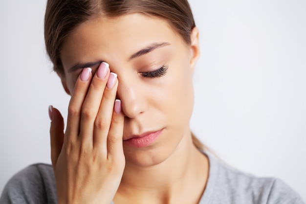 Wyczerpana młoda kobieta cierpi silny ból w pobliżu oczu