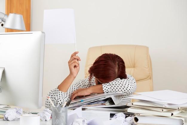 Wyczerpana młoda kobieta siedzi przy stole z twarzą na stosie dokumentów i pokazuje białą flagę